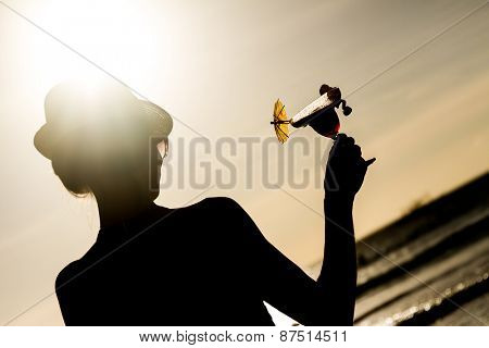 silhouette of young woman with glass of tropical cocktail on sunset sea background