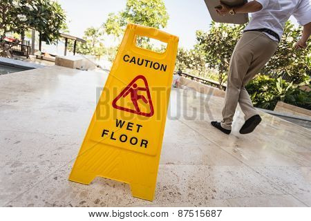 Yellow Caution Sign And Blur Of Paeple Walking On The Walkway
