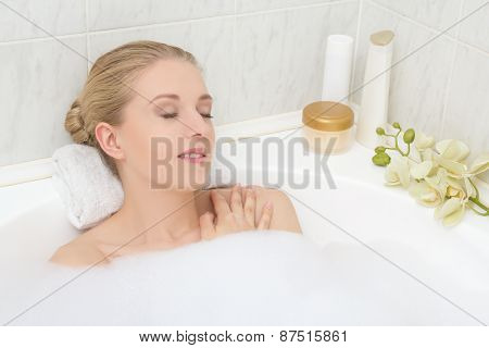 Young Woman Lying In Bath With Foam And Orchid Flower