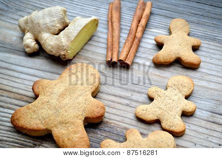 Gingerbread cookies in shapes of heart, star and man with cinnamon stick and ginger root on wooden t