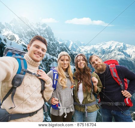 adventure, travel, tourism, hike and people concept - group of smiling friends with backpacks making selfie over alpine mountains background