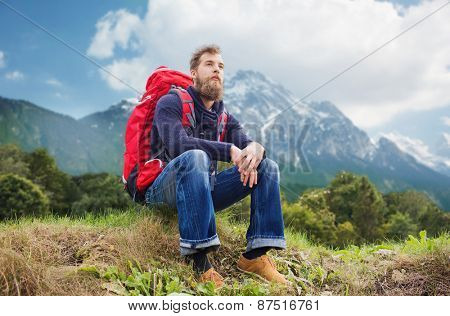 adventure, travel, tourism, hike and people concept - smiling man with red backpack sitting on ground over alpine mountains background