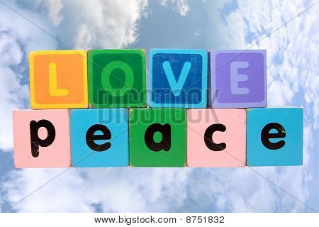 Love On Peace In Wood Play Block Letters Against Clouds