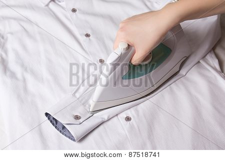 Iron In Female Hand Ironing Sleeve Of Cotton Shirt