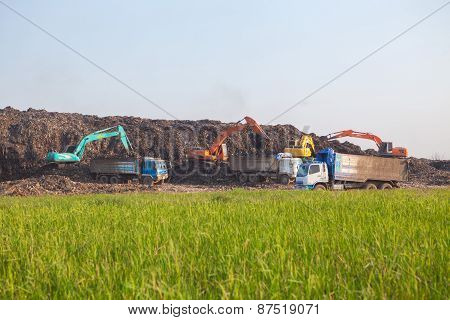 Garbage Trucks Work On The Landfill