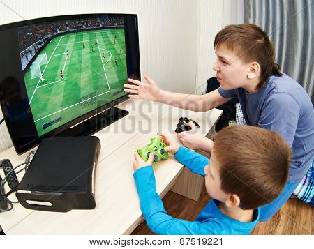 Children Playing On Games Console To Play Football