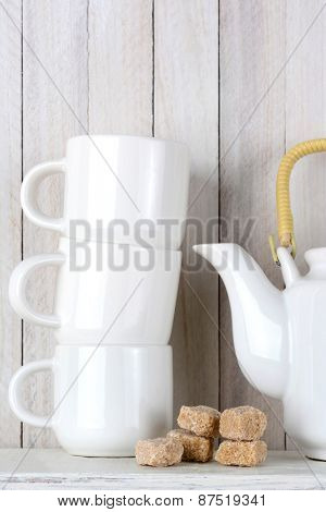 Closeup of a white ceramic tea set with natural brown sugar cubes, Vertical format on a rustic white wood kitchen setting.