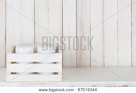 Closeup of a pair of salt and pepper shakers in a small wood box on a white wood rustic kitchen shelf. Horizontal format with copy space.