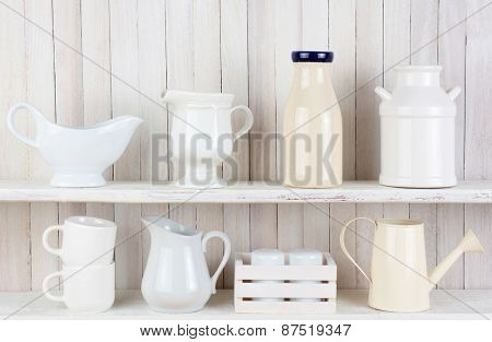 Closeup of two white wood rustic kitchen shelves with assorted household items. Various objects, include, salt and pepper shakers, cups, pitchers bottles and crockery.