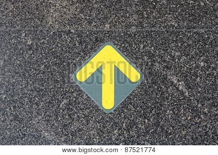 black cement floor with yellow arrow sign