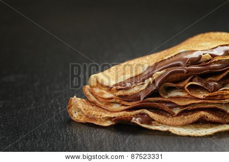 thin crepes or blinis with chocolate cream on slate