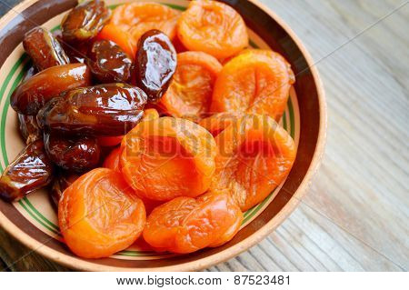 Dried apricots and brown dates fruit on wooden table