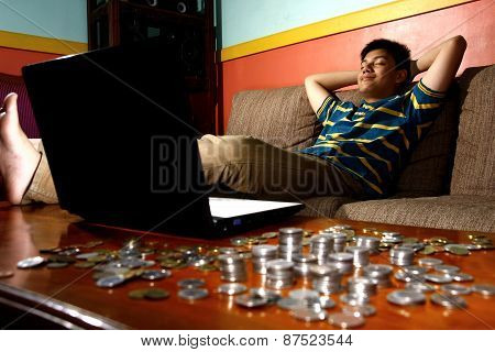 Asian Teen relaxing in front of laptop computer and a stack of coins
