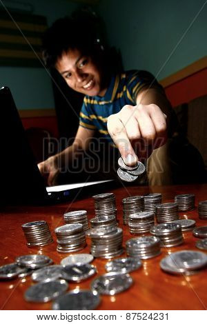 Asian Teen in front of laptop computer and piling on a stack of coins