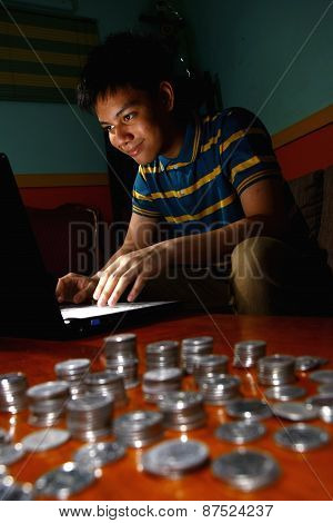Asian Teen in front of laptop computer and a stack of coins