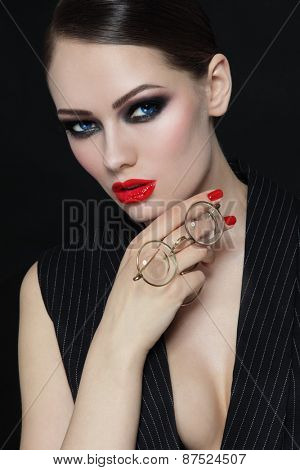 Young beautiful sexy woman with stylish make-up and vintage glasses in her hand