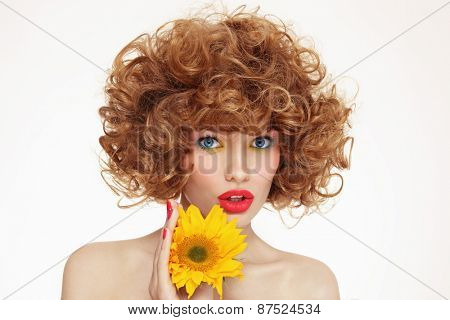 Portrait of young beautiful woman with curly hair and sunflower in her hands