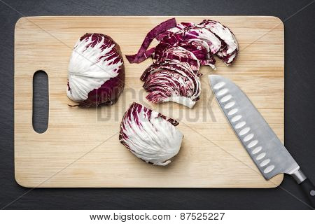 Purple cabbage cut on a chopping board with knife, isolated on stone plate.