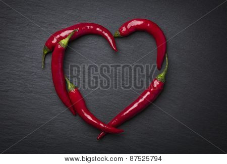 Red chili peppers in heart shape, indicating hot love for valentine's day, isolated on dark grey slate stone.
