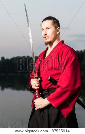 Man in ethnic samurai japanese clothing uniform with katana sword