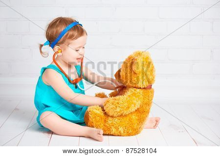 Girl Playing Doctor And Treats Teddy Bear