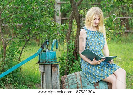 Blonde Student Girl In Garden Is Reading Book With Blue Cover