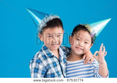 Little brothers in birthday hats