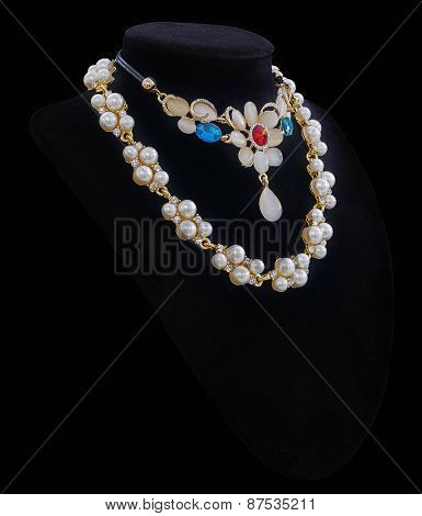 Gold and luxury pearl necklaces on black stand isolated in black background.