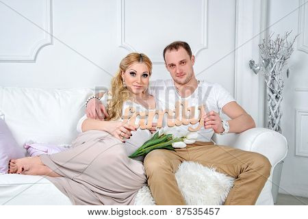 Happy family in white living room. Man and woman holding wooden word family together.