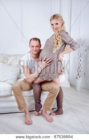 Happy young pregnant couple embrace each other on a sofa in white living room