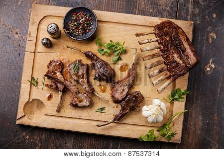 Roasted Lamb Ribs And Greens On Wooden Cutting Board On Dark Background
