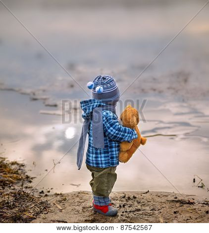 Small Child Standing On Lake Shore With His Teddy Bear...
