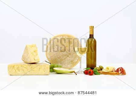 Various Types Of Cheese With Wine, Tomatoes, Basil, Olives, Ham, Grapes, Pears And Bread