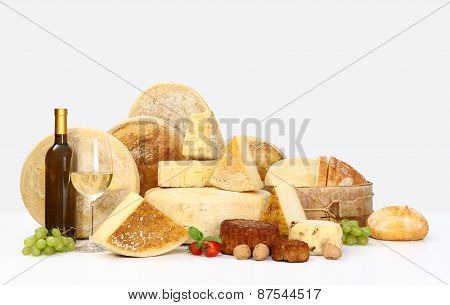 Various Types Of Cheese With Wine, Grapes, Tomatoes, Basil And Bread