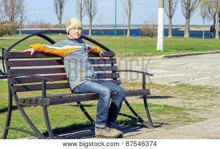 Boy Sitting On A Bench