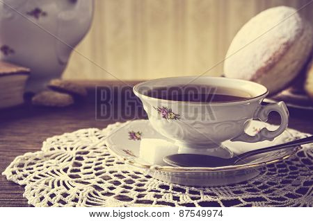 Doughnut With Cup Of Tea In Old-fashioned Room On Napkin