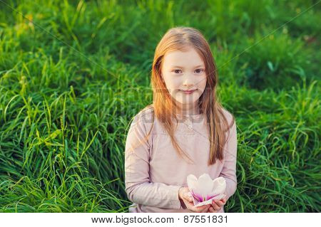 Outdoor portrait of a cute little girl on sunset, playing in the park with big magnolia flower