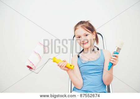Cute little girl sitting on a step ladder, holding a roller and brush