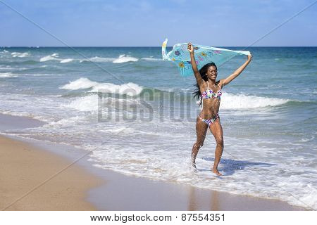 Young woman walking on the beach with a colored sarong