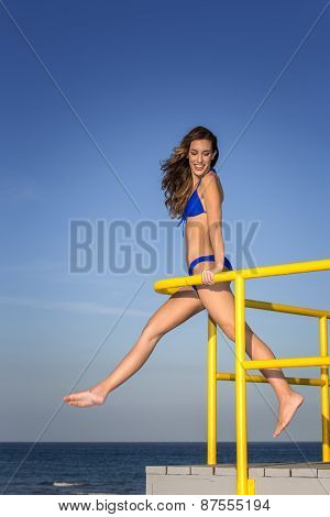 Young woman in bikini. Balancing on a railing at the beach.