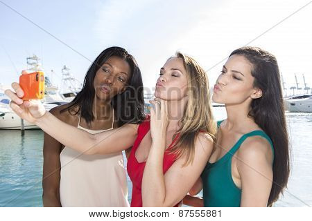 Portrait of three women taking duck-face selfies with a smartphone. Three friends posing for selfie