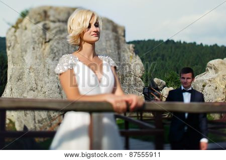 Groom Comes To The Bride Standing Near The Fence On The Mountain