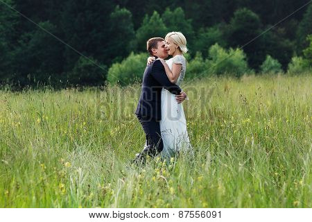 Wedding Couple Running On Green Grass At Sunset