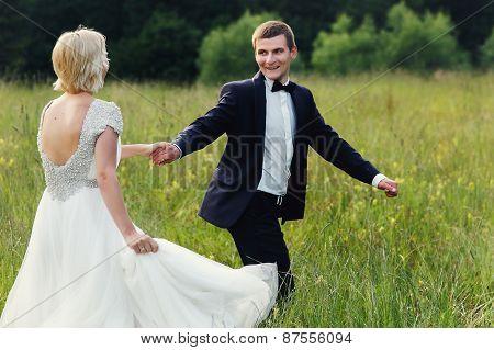 Wedding Couple Running On Green Grass At Sunset