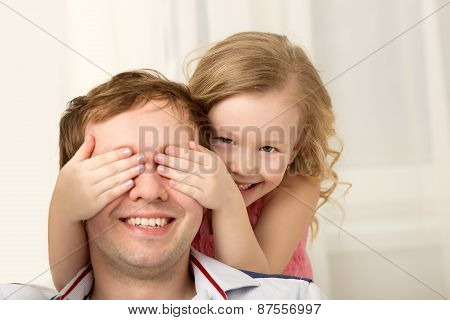 Daughter playing with father closing his eyes
