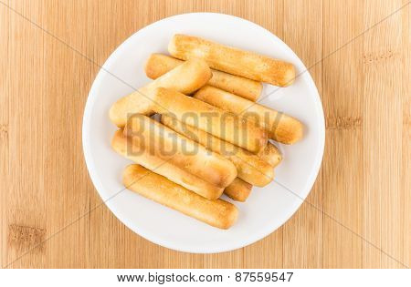 Bread Sticks In Saucer With Salt On Wooden Table