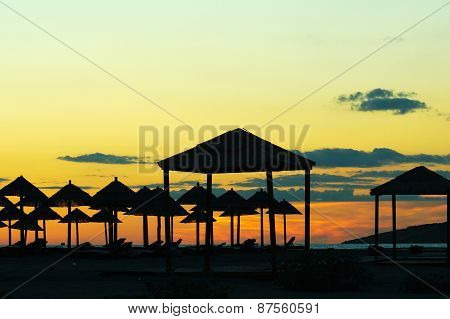 Sunset on the beach, the silhouettes of straw umbrellas and gazebos