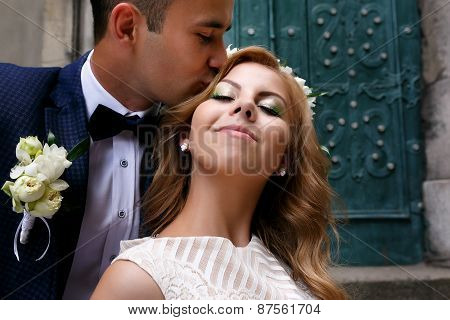 Portrait Of Bride And Groom Kissing Wife