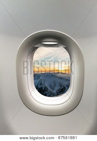 Looking Out The Window Of A Plane At The Mountains And Sunset