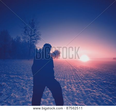 Man Standing On Field And Watching Sunrise